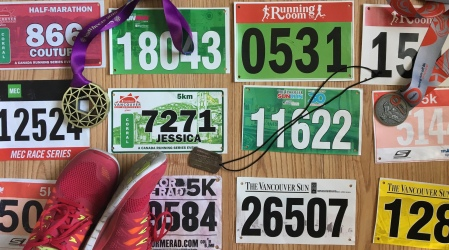 Flat lay of race bibs, medals, and running shoes