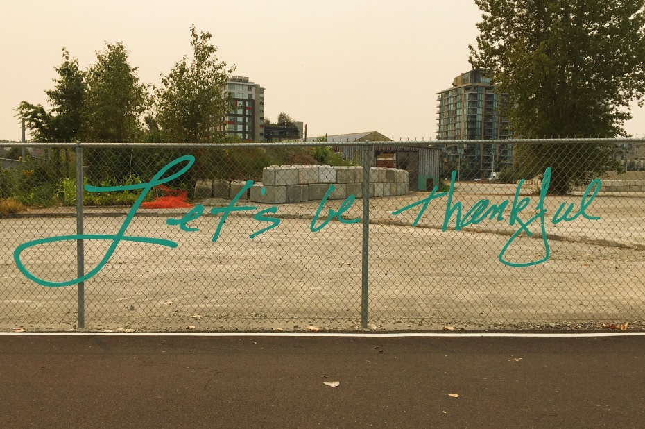 """Public art on a fence in Vancouver that says """"let's be thankful""""."""
