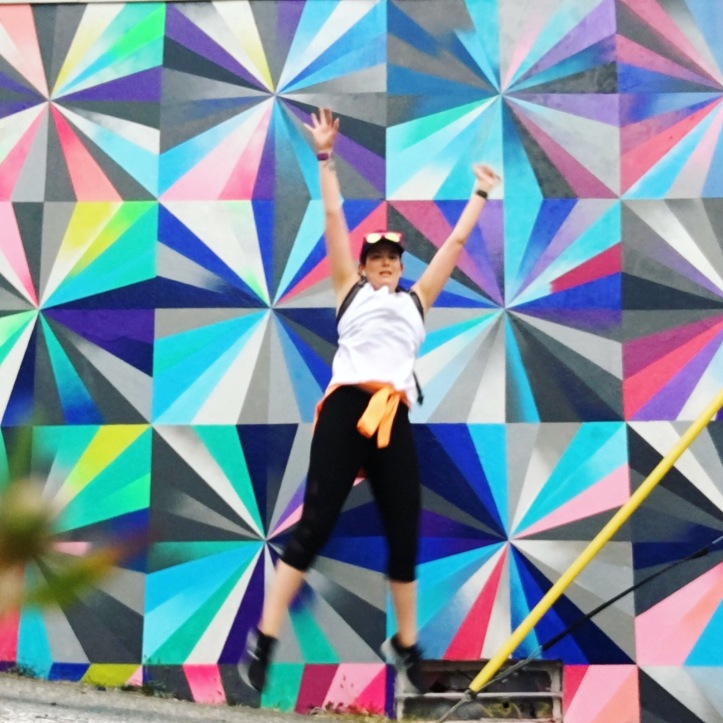 Jessica jumps in front of a colourful mural
