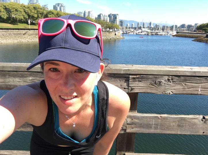 Girl takes a selfie mid-run on the False Creek Seawall facing east.